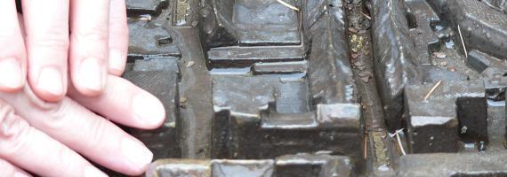 Das Bild zeigt eine Hand, die eine andere Hand zu dem Relief einer Stadt führt.